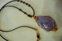 Hand polished lepidolite wrapped with copper on leather